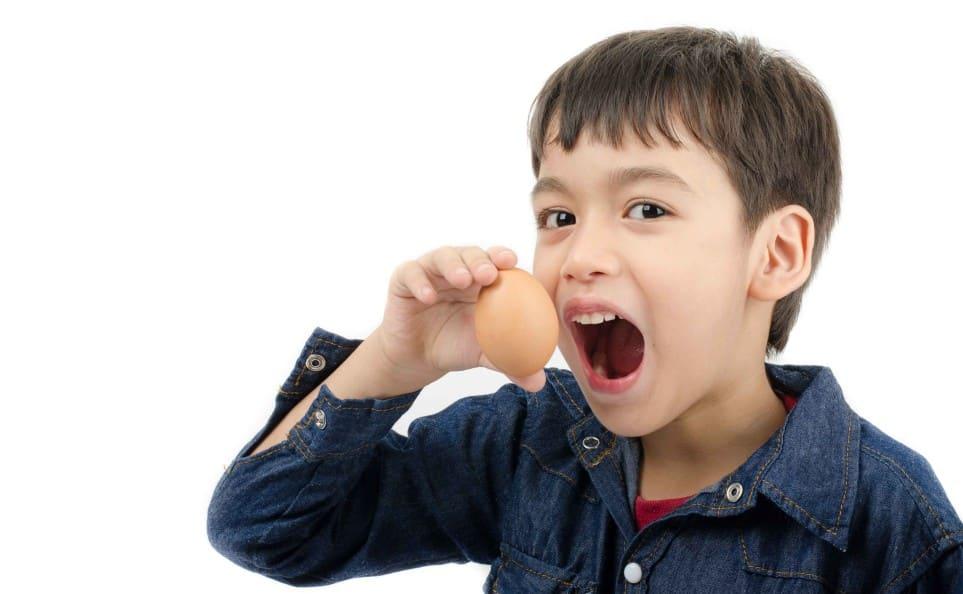 Boy holding up egg for brunch